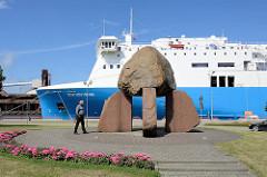 Steinskulptur an der Promenade vom Hafen in Ventspils / Windau, Lettland; bunte Plastikkuh auf dem Kai - im Hintergrund das Fährschiff Scottish Viking.