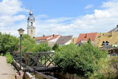 Blick von der Badegasse zur den Hausdächern an der Rückseite der Kirchenstrasse - Kirchturm der St. Nikolaus Kirche in Pretzsch / Elbe. Die Kirche wurde 1727 auf Veranlassung der damaligen Kurfürstin Christiane Eberhardine in barockem Baustil.