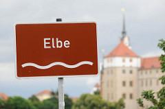 Flussschild Elbe - im Hintergrund Schloss Hartenfels in Torgau, Nordsachsen.