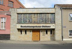Kubisches Geschäftshaus mit Buntglas-Oberlicht; Bestattungshaus in Torgau.