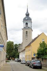 Blick durch die Kirchstraße zur St. Nikolaus Kirche in Pretzsch / Elbe. Die Kirche wurde 1727 auf Veranlassung der damaligen Kurfürstin Christiane Eberhardine in barockem Baustil umgestaltet - Entwurf Matthäus Daniel Pöppelmann.