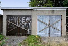 Alte Garagen mit Holztüren - die Tore sind mit Holzkreuzen vernagelt, Aufschrift Danke ihr Schweine -  Bilder aus Torgau / Elbe.