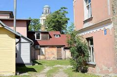 Hinterhof mit Kirchturm der St. Nikolauskirche in Ventspils / Windau, Lettland.