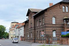 Backstein-Wohnhaus mit glasierten Ziegelbändern - im Hintergrund moderne Architektur; Straße der Jugend in Torgau.