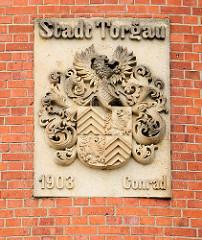 Relief an der Fassade vom Wasserturm - Wappen Stadt Torgau, Jahreszahl und Name des Architekten Conrad.