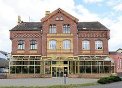 Historisches Ziegelgebäuden mit Dekorelementen  und gelb abgesetzten Klinkern; moderner Glasvorbau - Dommitzscher Straße in Torgau.