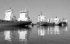 Mehrere Auflieger / temporär stillgelegte Frachtschiffe liegen an den Dalben in der Flussmitte der Norderelbe im Hamburger Hafen.