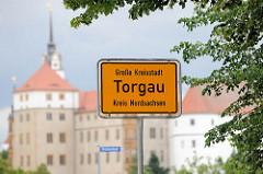 Stadtschild / Ortsschild - Große Kreisstadt Torgau, Kreis Nordsachsen; im Hintergrund das Schloss Hartenfels.