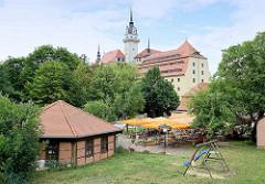 Grosser Biergarten mit Sonnenschirmen - dahinter das Schloss Hartenfels.
