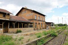 Stillgelegtes Empfangsgebäude / Bahnhofsgebäude von Dommitzsch; Gleise am Bahnsteig mit Gras bewachsen.