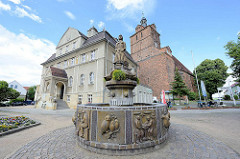 Gänsebrunnen am Marktplatz von Dommitzsch; im Hintergrund das Rathaus und die St. Marien Kirche.