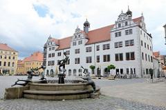 """Das Rathaus der Stadt Torgau ist von 1563 bis 1578 im Stil der Renaissance erbaut worden. Im Vordergrund der Brunnen """"Narren und Musikanten"""" - erbaut 2000, Künstlerin Erika Harbort."""