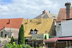 Hausdächer mit roten und gelben Dachziegeln - re. ein Fabrikschornstein mit einem Storchennest - Blick von der Badegasse zur Rückseite vom Pretzscher Markt.