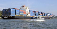 Der Containerfrachter Kota Latif fährt mit Container beladen auf der Elbe Richtung Hamburger Hafen - ein Sportboot überholt den Frachter.