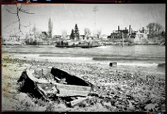 Scan Altes Holzboot / Ruderboot am Ufer vom Reiherstiegkanal - am gegenüber liegenden Ufer die Ruinen der ehem. Oelkers Werft in Hamburg Wilhelmsburg. (2000)
