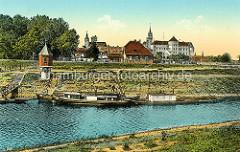 Historische Aufnahme vom Hafen in Torgau - Schiffe liegen am Ufer, Pegelturm und Panorama von Torgau mit Schloss Hartenfels.