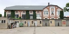 Industriearchitektur in Torgau - Jugendstilarchitektur mit Ziegelbändern; im Vordergrund Garagen.