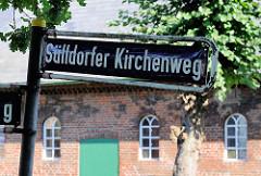 Straßenschild Sülldorfer Kirchenweg - im Hintergrund ein Bauernhof in Hamburg Sülldorf.