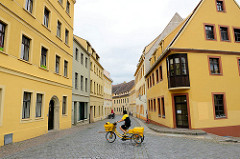 Blick in die Schloßstrasse von Torgau - gelbe, ockerfarbene Hausfassaden, Briefträgerin mit gelben Fahrrad.