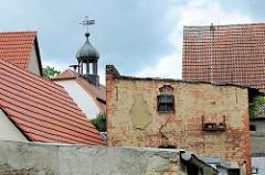 Schuppen mit Ziegelsteinfassade / Hausdächer, Turm vom Rathaus in Pretzsch (Elbe).