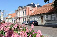Blühende Blumen am Strasserand - Wohnhaus mit Holzfassade - Geschäftshaus im Baustil Historismus - Tirgus iela in Ventspils / Windau, Lettland.