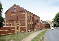 Renoviertes Backsteingebäude mit Ziegelmauer und gelb abgesetzten Bändern, erbaut ca. 1890 - Architektur in Wartenburg.