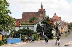 Blick zur Kirche St. Marien und dem Rathaus von Dommitzsch; Fahrradfahrer kreuzen die Straße.