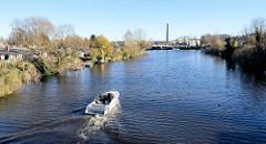 Blick von einer Fussgängerbrücke am  Bullehuser Kanal; Schrebergärten / Kleingarten am Wasser mit Bootsteg; im Hintergrund Industrieanlagen in Hamburg Billbrook - ein Sportboot fährt Richtung Bille.