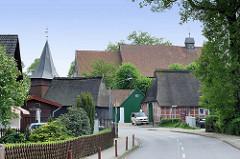 Blick durch die Bahnhofsstrße von Hittfeld zu historischen reetgedeckten Bauernhäuser und der Sankt Mauritiuskirche.