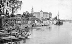Historische Ansicht vom Elbufer bei Torgau; Fischerkähne und Ewer liegen am Strand - im Hintergrund Schloss Hartenfels und die Elbbrücken.