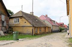 Traditionelle Architektur / Holzarchitektur - Holzhäuser an der Ģildes iela in Limbaži / Lemsal. Strasse mit Kopfsteinpflaster und schmalen Fußweg.