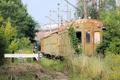 Verrostete, stillgelegte Personenwaggons beim Güterbahnhof Toruń, Prellbock und hohes Gras - Rankpflanzen überwuchern den Eisenbahnwagen.