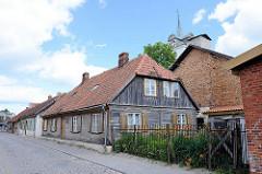 Typische Holzhäuser, Wohnhäuser mit Holzfassade und Fensterluken - Kuldīga / Lettland.
