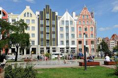 Moderne Neubauten - der historischen Bauweise von Elbląg / Elbing nachempfunden. Brunnen am Kirchvorplatz der Kathedrale St. Nikolai.