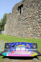 Burg des Livländischen Ritterordens aus dem 13. Jahrhundert in Valmiera, Lettland. Die Anlage wurde im Nordischen Krieg 1702 zerstört und ist nur als Ruine erhalten. Im Vordergrund eine modern / avantgardistisch bemalte bunte Sitzbank.