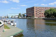 Blick über den Hafen in Elbląg / Elbing - Sportboote am Anleger, alte historische Industriearchitektur.