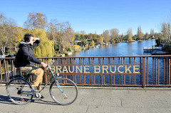 Radfahrer an der Braunen Bücke in Hamburg Rothenburgsort; Schrebergärten / Kleingärten am Ufer der Bille.