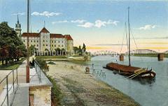 Historisches Foto von der Elbpromenade in Torgau - ein Elbkahn liegt vor Anker, Laufstege führen zum Ufer. Im Hintergrund Schloss Hartenfels und die Elbbrücke.