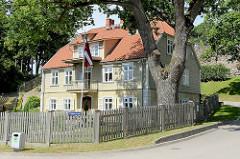 Einstöckiges Wohnhaus mit Holzfassade und Krüppelwalmdach auf dem Burgberg von Valmiera; die Burgmauer ist im Hintergrund zu erkennen.