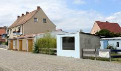 Freistehende Garagen, rechteckiges, flaches Steingebäude mit großem Fenster - Straße mit Kopfsteinpflaster; Am Hafen von  Mühlberg / Elbe.