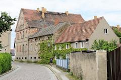 Alte Wohnhäuser mit Putzfassade, teilweise abgeblättert - schmale Straße in Mühlberg / Elbe.