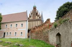 Historische Mauer, ehem. Abtei mit Nonneneingang - 1717 zum Herrenhaus umgebaut. Im Hintergrund die Klosterkirche Marienstern in Mühlberg / Elbe. Das Zisterzienserinnenkloster wurde 1228 gegründet.