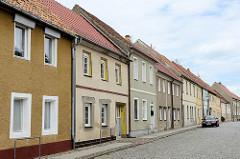 Einstöckige Wohnhäuser mit verputzter, teilweise farbiger Fassade - Kopfsteinpflaster, Mühlberg / Elbe.