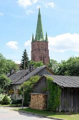 Kirchturm der Sankt Annen Kirche in Kuldīga / Lettland - erbaut 1904 - Architekt Wilhelm Neumann; Holzschuppen mit Feuerholz im Vordergrund.