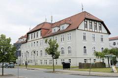 Mehrstöckiges Gebäude mit Krüppelwalmdach in der Reinhold Kirsten Straße; jetzt Sitz Sozialer Dienste + Seniorenheim.