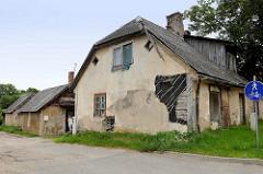 Verfallenes Wohnhaus mit Wellplatten gedeckt - holzverkleidetes Dachfenster, abbröckelnde Putzfassade zeigt Bretterwand. Impressionen aus der lettischen Stadt Cēsis.