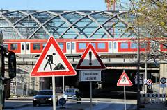 Blick von der Zweibrückenstraße zur Bahnbrücke, der ehem. Zollgrenze im Hamburger Freihafen; ein S-Bahn Zug fährt Richtung Hauptbahnhof, im Hintergrund das Dach der Haltestelle Elbbrücken.