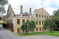 Historisches Gebäude am Alekšupīte-Bach in Kuldīga; das Dach ist abgerissen, die Fassade wird mit Eisenträgern gestützt.