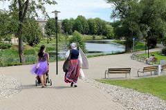 Frau in Tracht, Mädchen mit Kinderwagen im Stadtpark / Mühlensee, dzirnavu ezerins von Valmiera, Lettland.