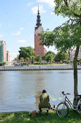 Blick über den Fluß Elbing zur Promenade und der katholischen St. Nikolaikirche - Baubeginn 13. Jahrhundert. Ein Angler sitzt am Flussufer, sein Fahrrad steht an einen Baum gelehnt.